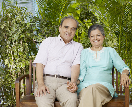 Old couple holding hands sitting on wooden bench