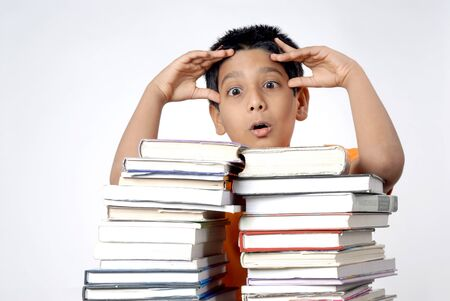 Boy in tension holding head standing with stack of books Banco de Imagens