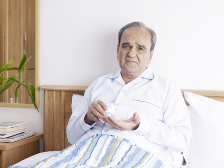 Old man in sad mood holding pill bottle sitting on bed