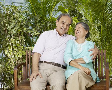 나무 벤치에 앉아 껴안은 오래 된 커플