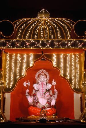 Idol of lord Ganesh elephant headed god kept in gaily decorated frame of illuminated lights,Ganpati festival at Pune,Maharashtra,India