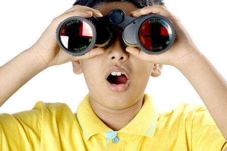 Young boy looking through binocular seeing wonder and surprising expression Stock Photo