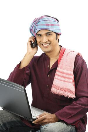 부유 한 인도의 농부가 어깨에 붙어있는 다른 머리에 감추면을 노트북과 전화 통화 스톡 콘텐츠