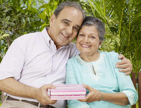Old couple embracing holding present box