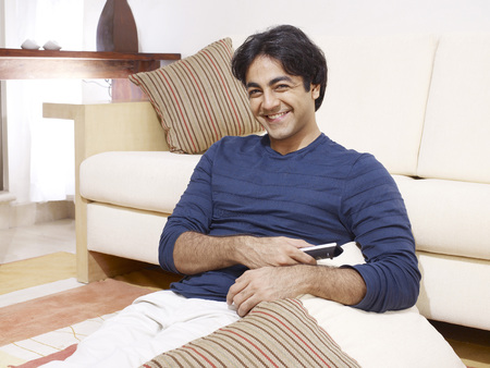 contemporary living room: Young man holding remote control