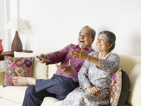 Old couple expressing with hands using remote control Stock Photo