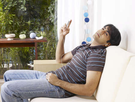 contemporary living room: Young man listening to music on headphones resting on sofa LANG_EVOIMAGES