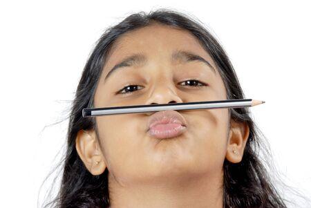 Young naughty girl kept pencil above lips