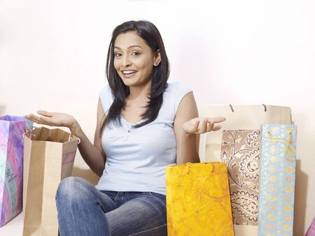 contemporary living room: Young lady expressing with hands and colourful shopping bags