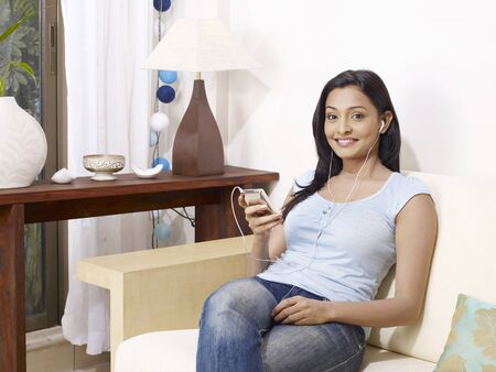 contemporary living room: Young lady listening to music on headphones sitting on sofa