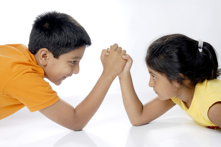 clashes: Boy and girl showing arm wrestling looking at each other LANG_EVOIMAGES