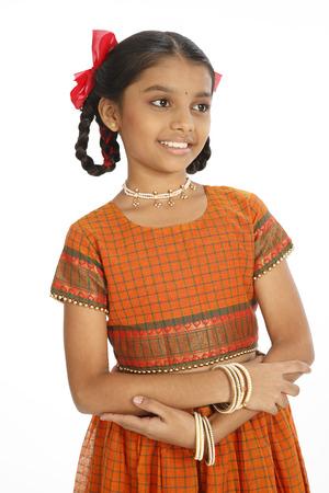 10 살짜리 농촌 소녀가 잘 차려 입고 몸을 접고 몸 앞에서 지켰다.