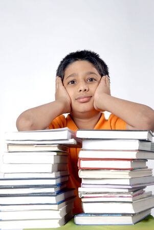 Boy thinking kept both hand palm on cheek standing with stack of books