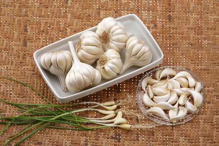 Vegetables and Indian spices,garlic bulb cloves with root allium sativum on brown background