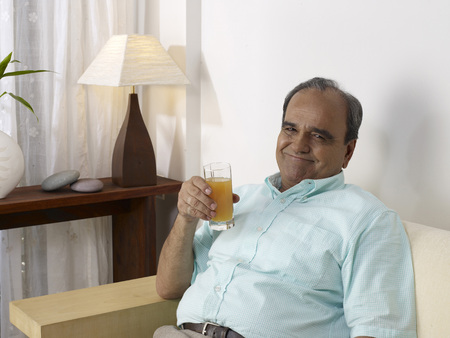Old man holding glass of juice sitting on sofa