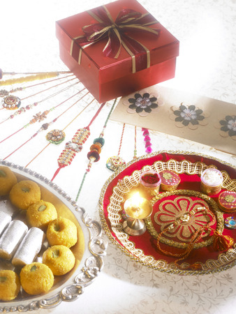 Rakhis sweets chocolates diya arrange in thali with gift box on Rakshabandhan festival