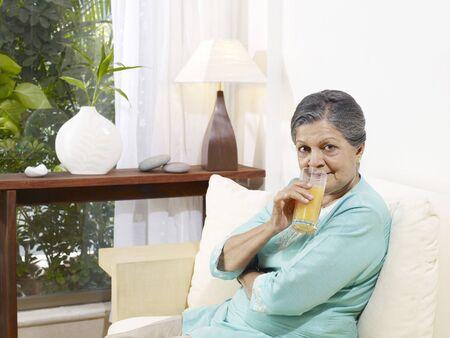 Old lady drinking juice sitting on sofa Stock Photo
