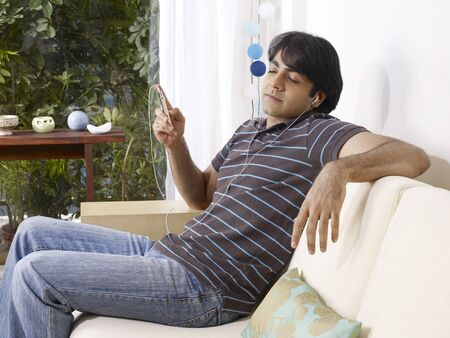 contemporary living room: Young man closed eyes listening to music on headphones sitting on sofa LANG_EVOIMAGES