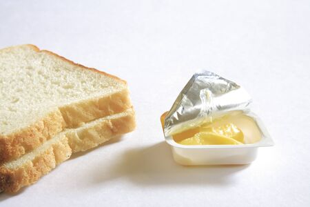 Breakfast,bread and butter in half open container on white background Stock Photo - 85791193