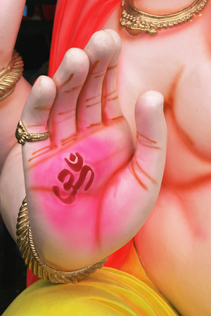 Right palm of idol of lord ganesha elephant headed god with om meaning welcome painted on it,Pune,Maharashtra,India
