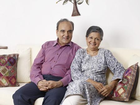 Old couple sitting on sofa Stock Photo
