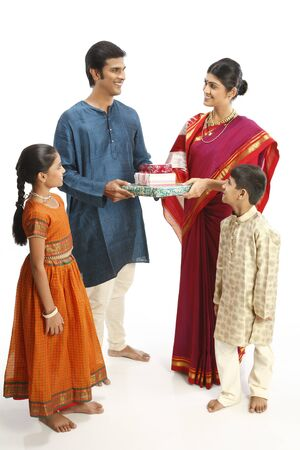 Rich rural farmer giving gift boxes to wife children standing with them