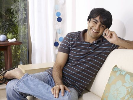 Young man talking on mobile sitting on sofa Stock Photo