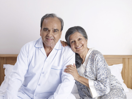 Old couple sitting close to each other on bed