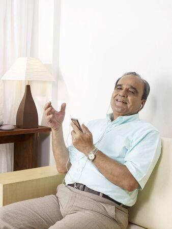 Old man listening to music on headphones sitting on sofa