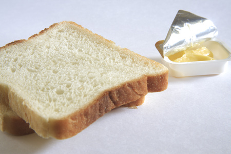 Breakfast,bread and butter in half open container on white background Stock Photo