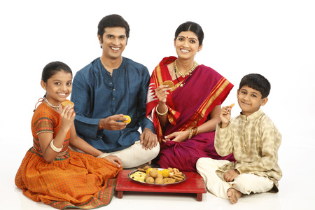 Rich rural farmer family sitting together with snacks kept in plate on wooden seat