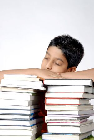 Boy resting on both hands kept on stack of books