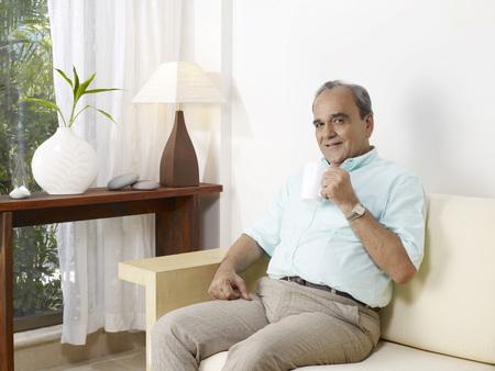 Old man showing white mug sitting on sofa