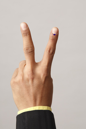 Executive showing voting mark on Index and middle finger
