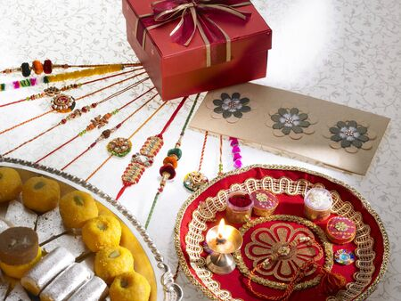 Rakhis sweets chocolates diya arrange in thali with gift box on Rakshabandhan festival