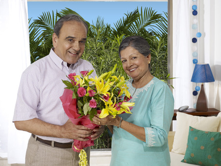 drawing room: Old couple holding bouquet looking at camera LANG_EVOIMAGES