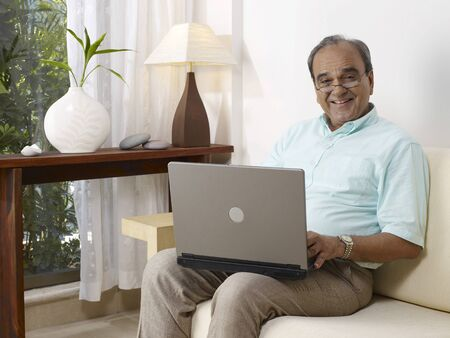 Old man with laptop sitting on sofa Stock Photo