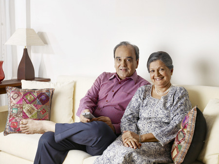 Old couple using remote control sitting on sofa Stock Photo - 85791729