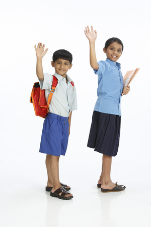 Rural boy and girl going to school saying buy