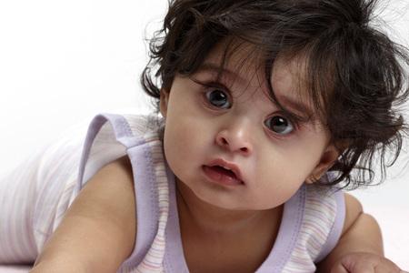 2a1b05bbef Joyful baby girl in dress lie down Stock Photo