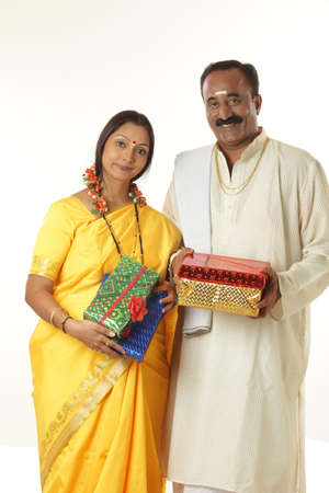 South Indian husband and wife holding gifts in hands Stock Photo