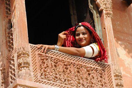 Rajasthani lady looking through jharoka,Rajasthan,India Stock Photo