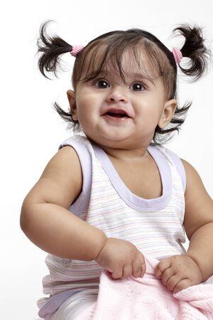 Joyful baby girl in dress sitting looking above 版權商用圖片