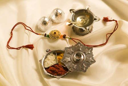 Concept,Rakhi sweet kumkum haldi akshata aarti lamp on silk cloth for Rakshabandhan festival Stock Photo