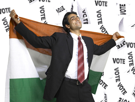 Executive holding national flag of India on his backside with vote stripes in background