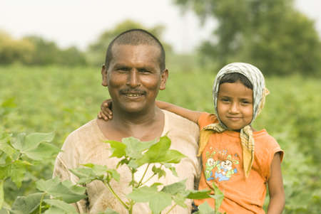 Farmer with daughter hold in hand and standing in cotton field,village Vaitagvadi,Parbhani,Marathwada,Maharashtra,India