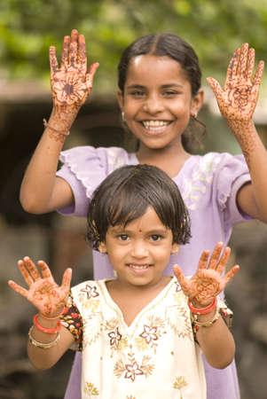 Ten and six year old girls showing mehendi design on both hand palms in Salunkwadi,Ambajogai,Maharashtra,India Stock Photo