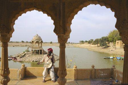 dhoti: Folk musician playing musical instrument at Gadsisar Gadisar lake,Jaisalmer,Rajasthan,India