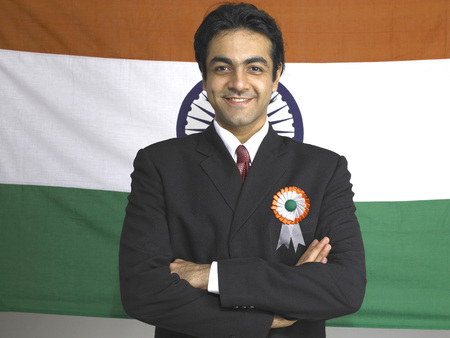 Executive folded hands standing in front of national flag of India