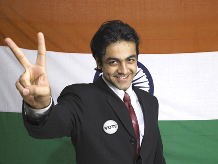 Executive showing victory sign standing in front of national flag of India